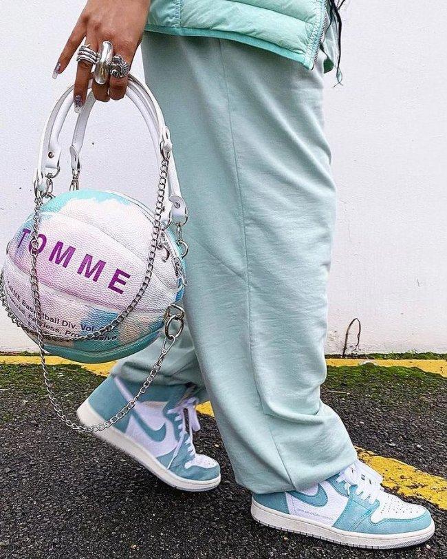 Foto de uma mulher da cintura para baixo. Ela usa uma calça moletom azul, tênis com detalhes brancos e azul e segura uma bolsa branca e azul em formato de bola de basquete.