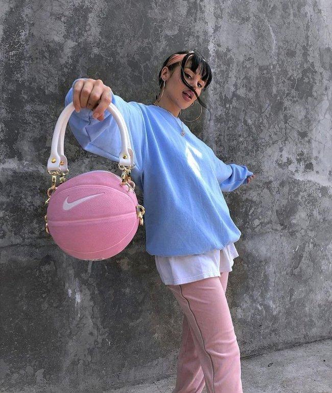 Foto de uma mulher encostada em um muro. Ela usa uma camiseta oversized branca, moletom azul como sobreposição, calça rosa e bolsa em formato de bola de basquete rosa. Ela está de braços abertos, olha para a câmera e não sorri.