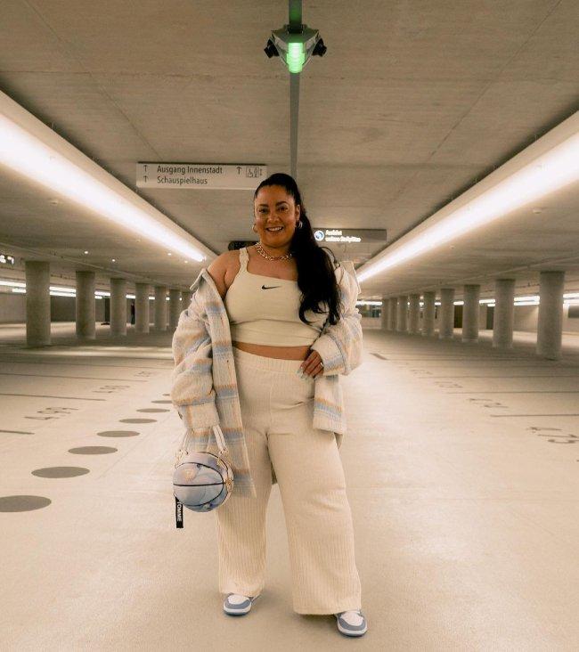 Foto de uma mulher no estacionamento. Ela usa um top e uma calça na cor creme, tênis nas cores azul e branca e segura a bolsa em formato de bola de basquete na mão direita. Ela olha para a câmera e sorri.