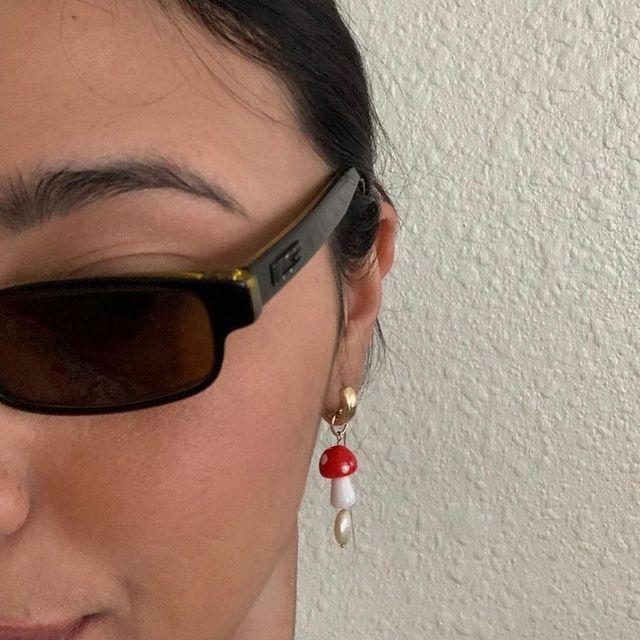 Foto da parte do rosto de uma mulher. Ela usa um óculos de sol vintage e um brinco em formato de cogumelo vermelho.
