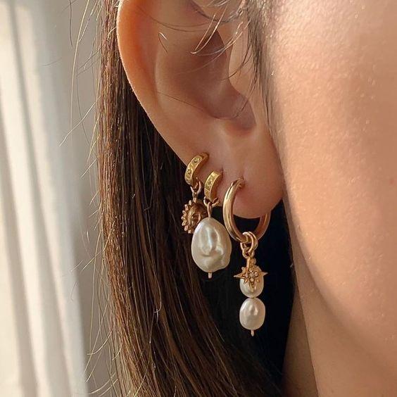 Foto da orelha de uma mulher com três brincos dourados, dois deles têm pingente de pérolas.