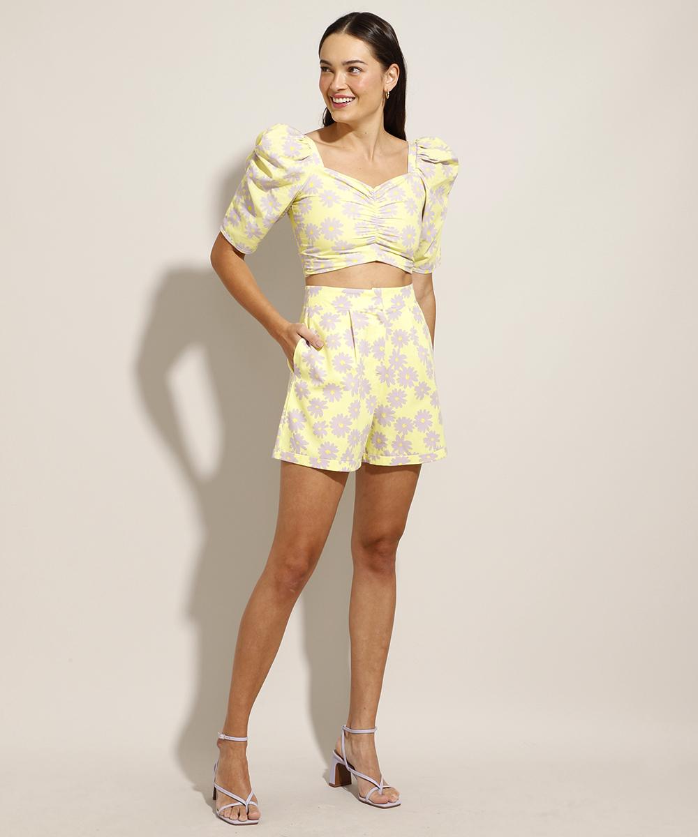 Modelo usando top cropped amarelo floral com mangas bufantes, short na mesma estampa e sandália lilás. Ela está com uma das mãos no bolso, olhando para o lado e sorrindo.