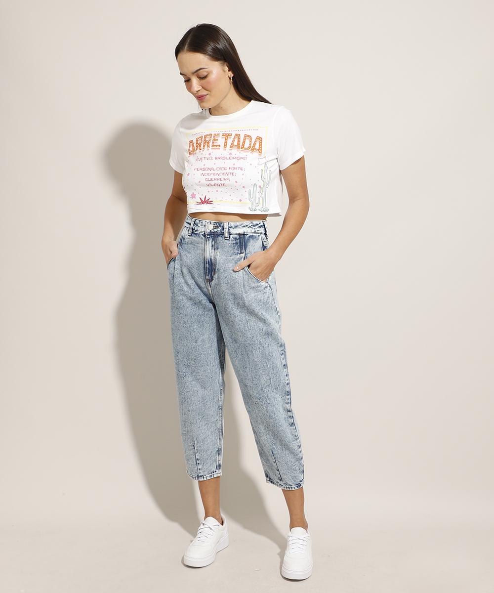 Modelo usando top cropped branco estampado, calça jeans baggy e tênis branco. Ela está olhando para baixo com as duas mãos nos bolsos.