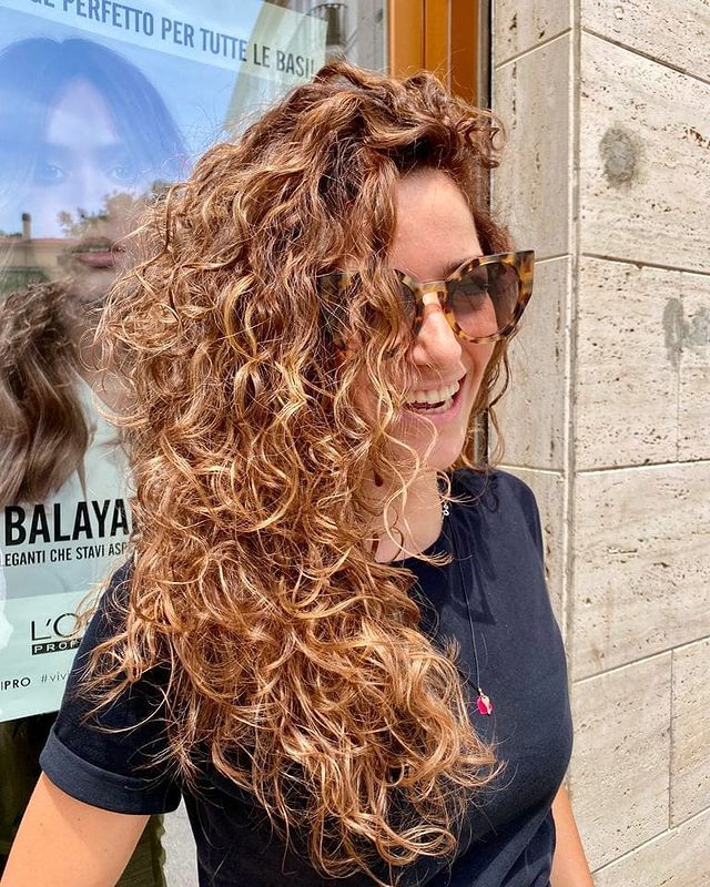 Jovem sorridente usando óculos escuros, com cabelos cacheados balançando com o vento e usando camiseta preta em frente a vidraça de um salão de cabeleireiro.