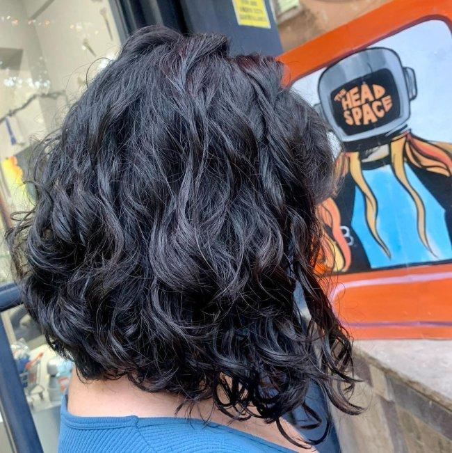Mulher está de costas e não conseguimos ver seu rosto, somente seu cabelo com corte bob na cor preta e com assimetria