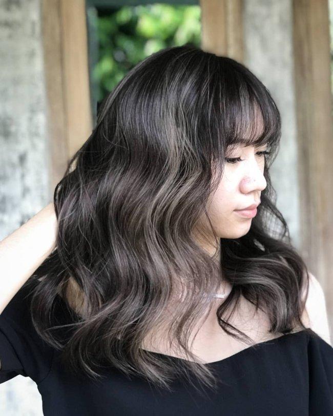 Jovem com os olhos fechados olhando para o lado direito, exibindo seu cabelo preto com nuances em cinza. Sua expressão é séria e ela usa camisa preta.