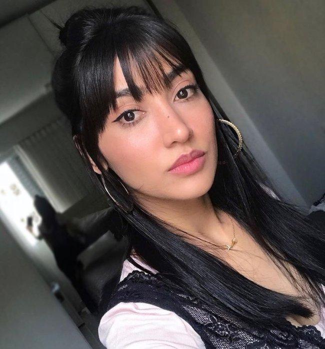 Selfie de uma mulher. Ela usa uma blusa cor creme com detalhes de renda preta, maquiagem natural, brinco de argola e cabelo com franja desfiada solto. Ela olha para a câmera e não sorri.