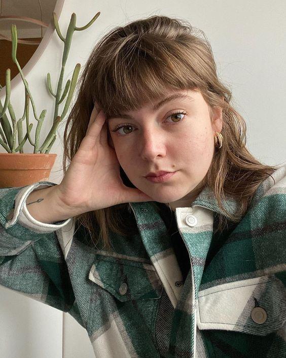 Selfie da influenciadora Marieli Mallmann. Ela usa um casaco de estampa xadrez e cabelo com franja reta solto. Ela segura o rosto com mão direita, olha para a câmera e não sorri.