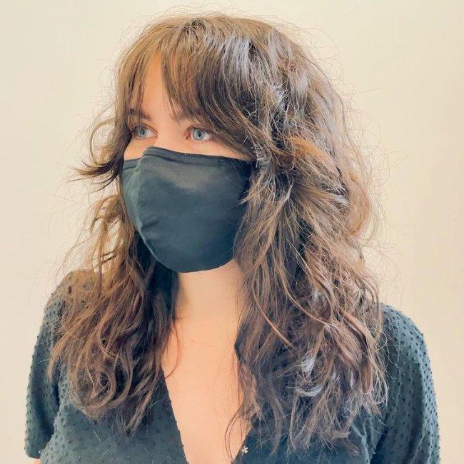 Jovem usando máscara de proteção preta e cobrindo sua expressão facial. Ela veste uma blusa decotada e olha para o lado esquerdo.
