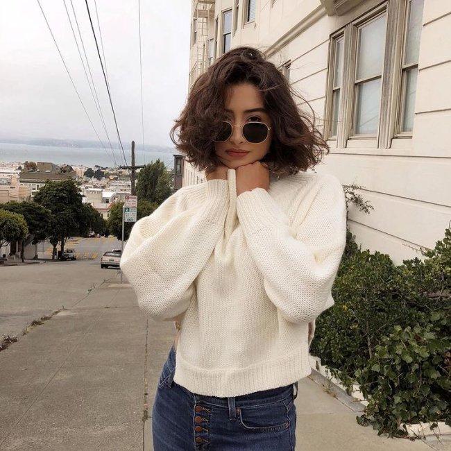 Foto de uma mulher na calçada. Ela usa uma calça jeans, casaco branco, óculos de sol e cabelo ondulado solto em um corte reto acima do ombro. Ela olha para a câmera e não sorri.