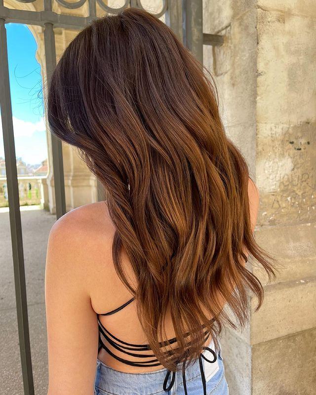 Jovem de costas mostrando seus cabelos castanhos ondulados ela usa regata marrom.