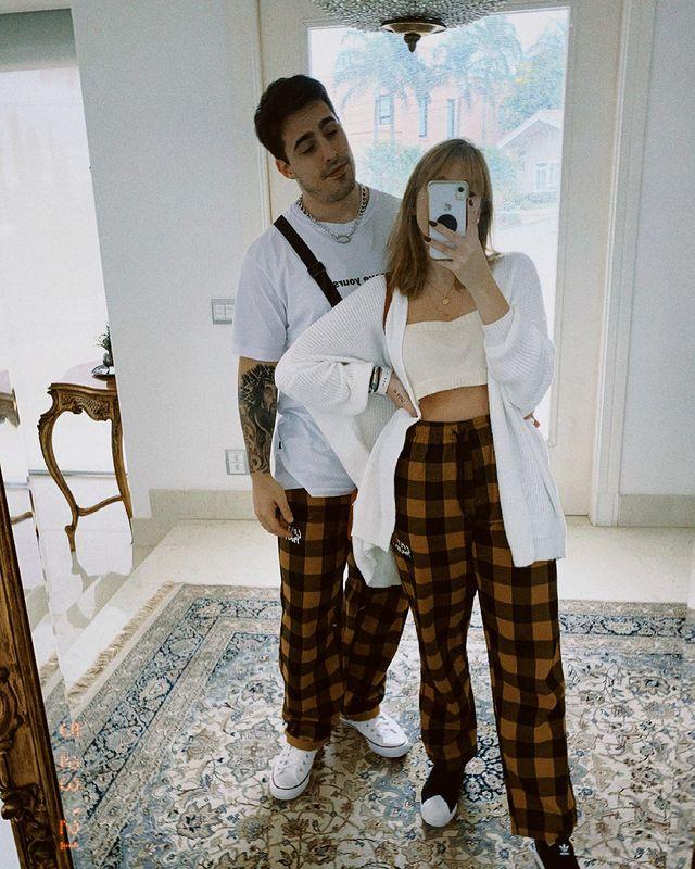 Casal posando em frente ao espelho, rapaz usa camisa branca e calça xadrez amarela e preta, e a menina cropped branco e calça xadrez preto e amarelo.