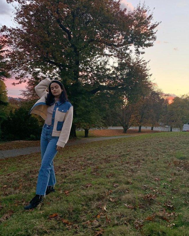 Camila Mendes com calça jeans e jaqueta