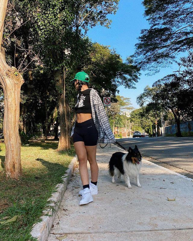 Foto de uma mulher em uma calçada com um cachorro. Ela usa uma camiseta preta, shorts preto, camisa xadrez, boné verde e tênis branco. Ela olha para trás.