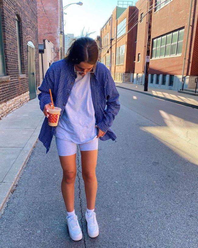 Foto de uma menina na rua. Ela usa uma camiseta cinza oversized, biker shorts, camisa xadrez azul e tênis branco. Ela olha para baixo e segura um copo de café.