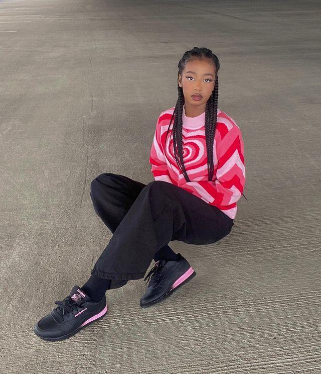 Foto de uma mulher sentada no chão de um estacionamento. Ela usa blusa rosa de gola alta com estampa de coração, calça preta e tênis preto. Ela olha para a câmera e não sorri.
