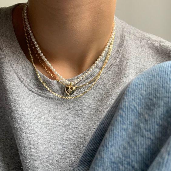Foto do pescoço de uma pessoa. Ela usa um colar de pérolas com pingente de coração, uma corrente dourada e blusa cinza.
