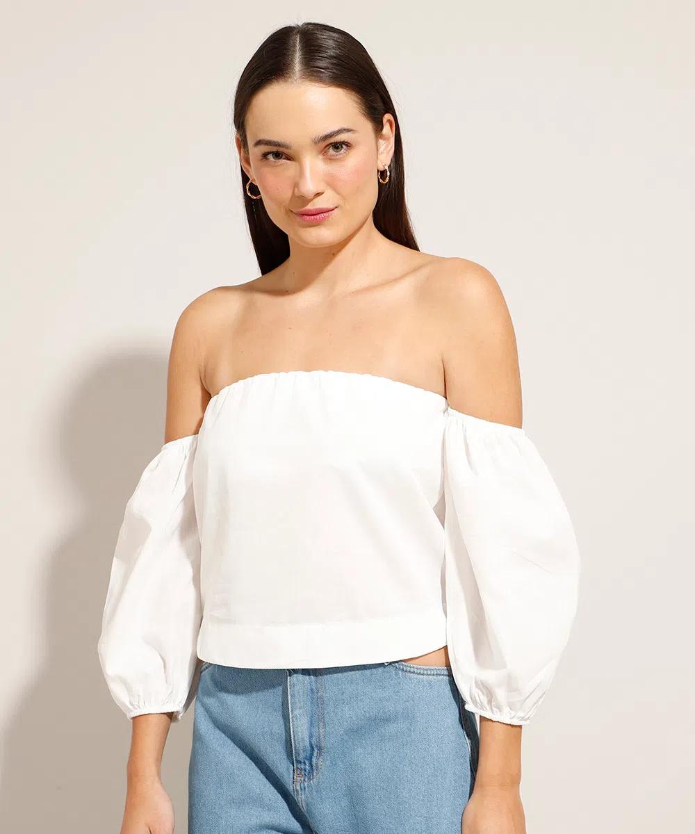 Modelo usando blusa cropped branca com mangas bufantes e, na foto, dá para ver uma parte da calça jeans. Ela está olhando para a câmera com expressão facial séria.