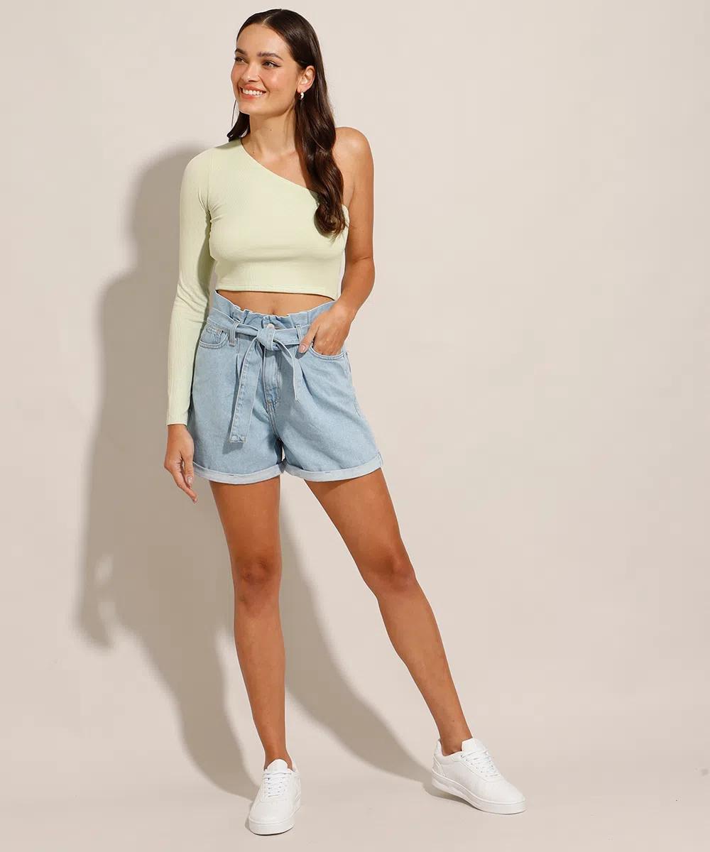 Modelo usando top cropped branco de uma manga longa só na cor verde pastel, short jeans de cintura alta e tênis branco. Ela está olhando para o lado, sorrindo e com uma das mãos no bolso.