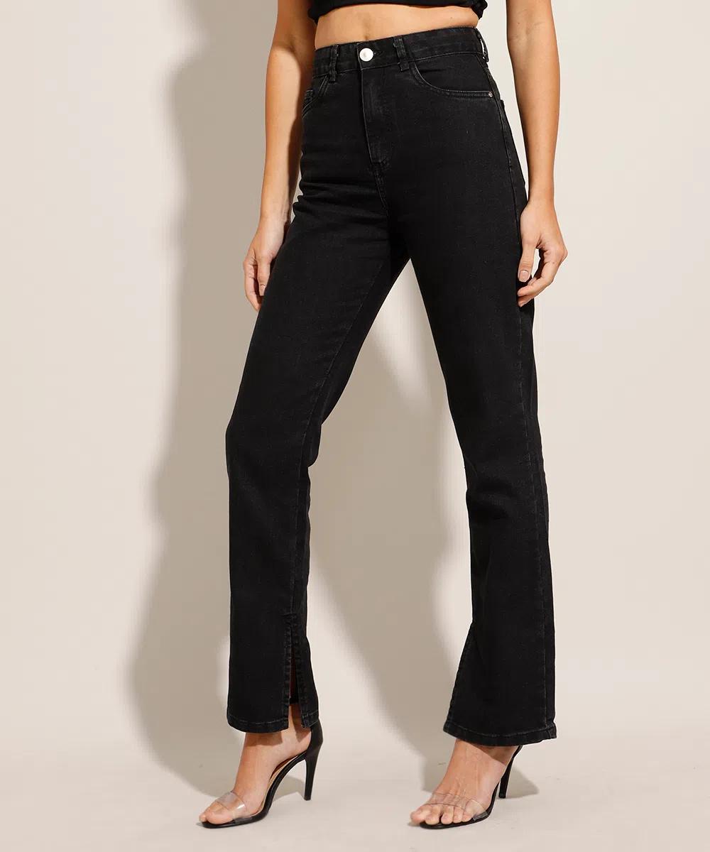 Modelo usando calça jeans preta com sandália preta de salto alto. Na foto, dá apenas para ver a perna e os pés.