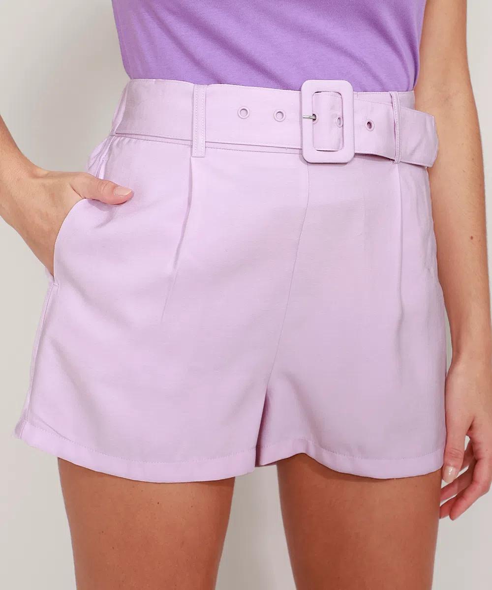 Short de alfaitaria lilás com cinto. Na foto, dá para ver a mão da modelo no bolso, um pedaço das pernas dela e da camiseta lilás que ela está usando.