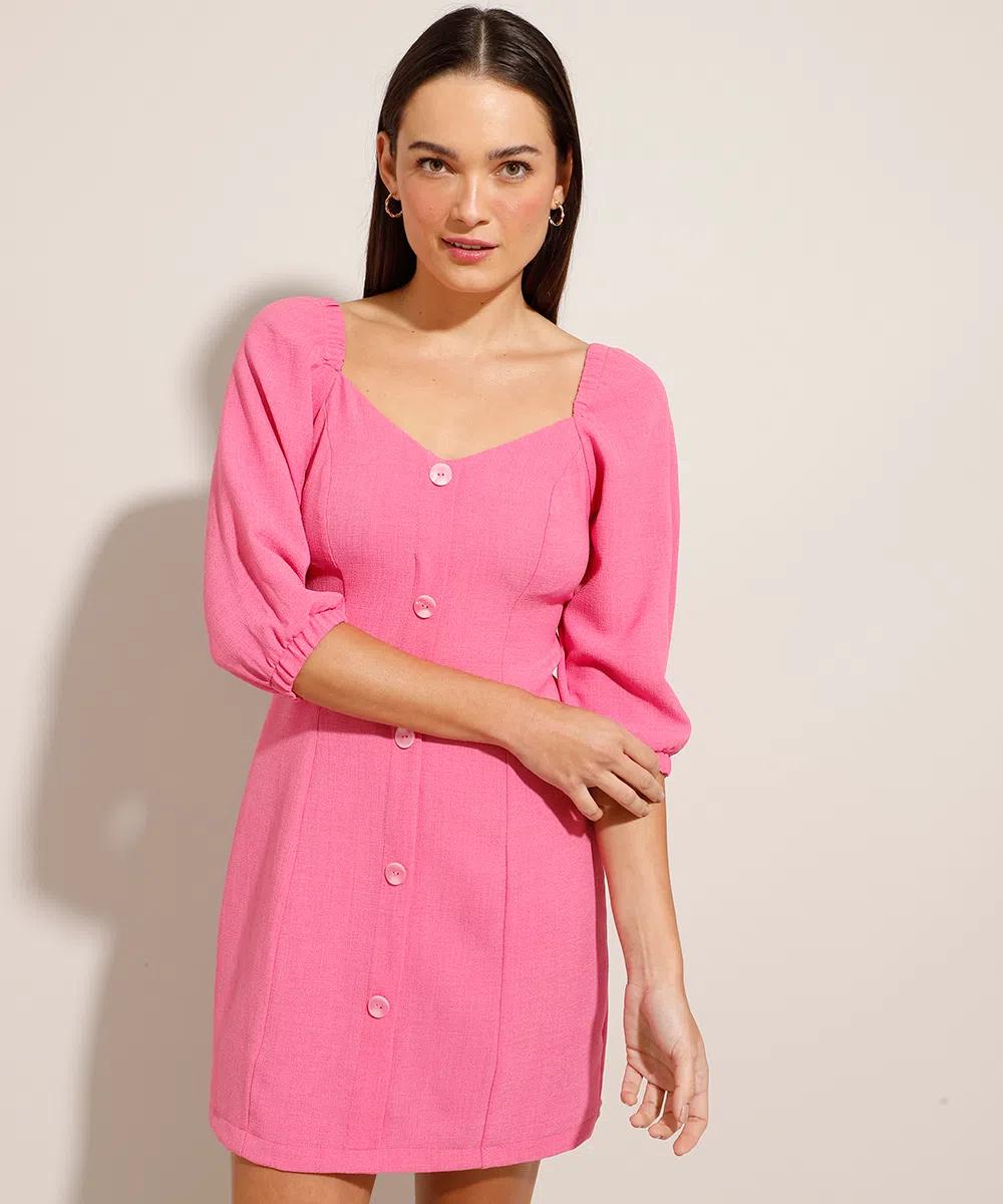 Modelo usando vestido rosa de mangas bufantes, decote princesa e botões frontais. Ela está olhando para a câmera com expressão facial séria e um dos braços está dobrando encostando no outro.