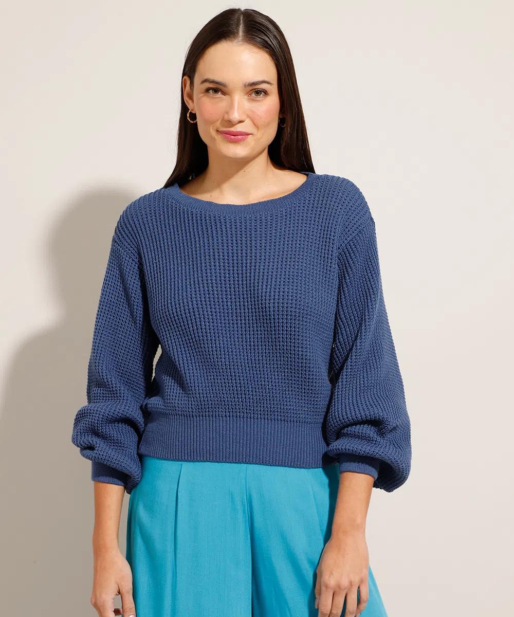 Modelo usando suéter azul-marinho de mangas bufantes e, na foto, também dá para ver uma parte da calça azul clara. Ela está olhando para a câmera com um leve sorriso sem mostrar os dentes.