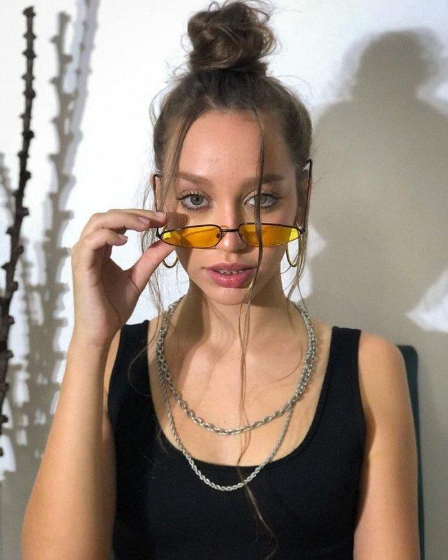 Jovem posando com expressão séria usando óculos amarelo, colares, regata preta.
