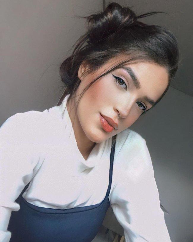 Selfie de jovem com expressão séria usando blusa banca de gola alta.