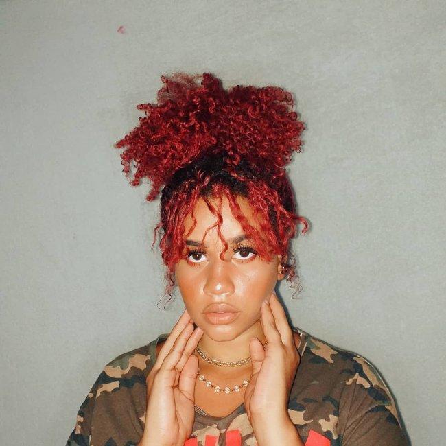 Jovem posando com expressão séria em frente a parede branca, ela apoia suas duas mãos em seu rosto e usa blusa segunda pele preta.