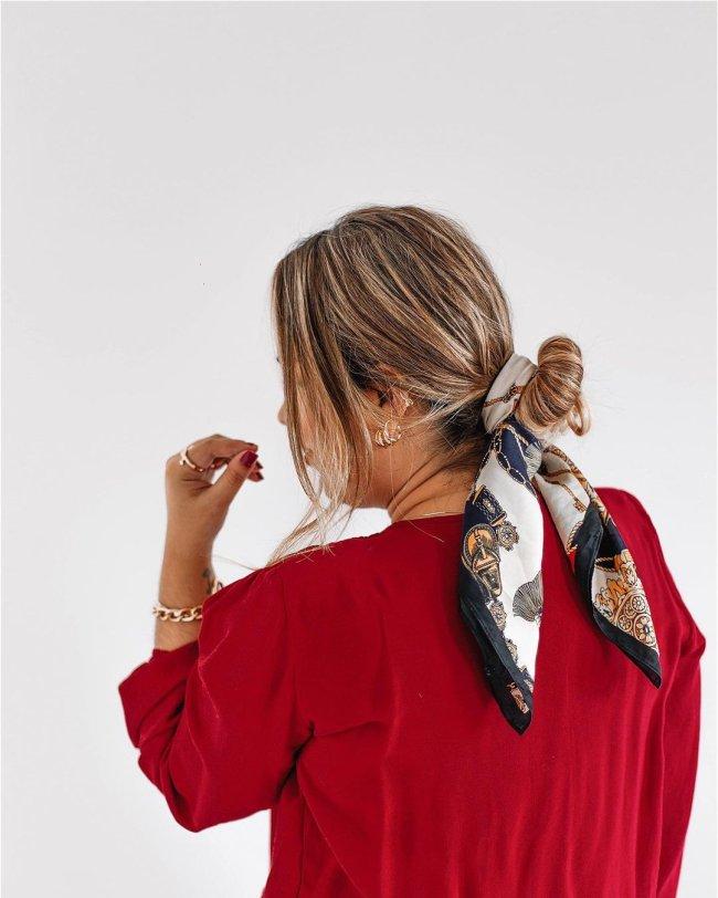 Foto de jovem de costas, usando blusa vermelha e lenço para amarrar seu coque.