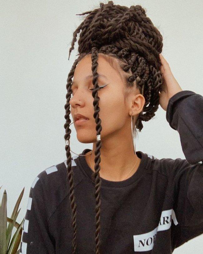 Jovem posando olhando para o lado com tranças por todo o cabelo formando um coque no topo da cabeça. Sua expressão é séria.