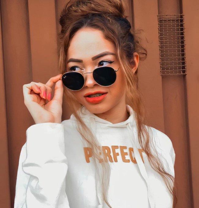 Jovem usando óculos escuros, com uma expressão séria, usando blusa de moletom branca com a palavra PERFECT escrita em dourado.