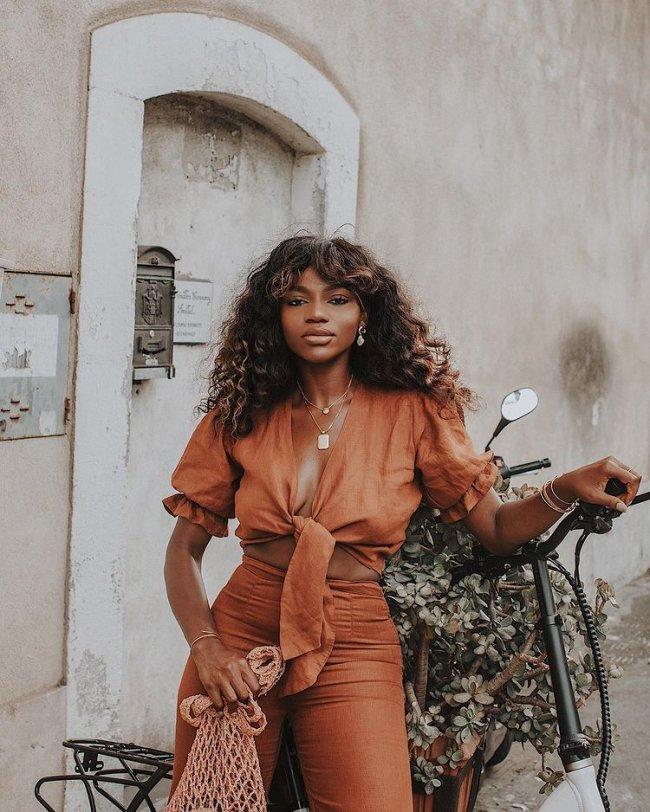 Jovem posando com look laranja monocromático, em apoiada em uma bicicleta com flores, ainda conseguimos ver uma porta branca atrás dela.