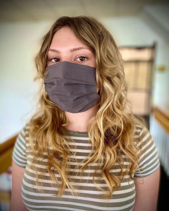 Jovem usando máscara de proteção preta e cobrindo sua expressão facial. Ela veste uma camiseta listrada.