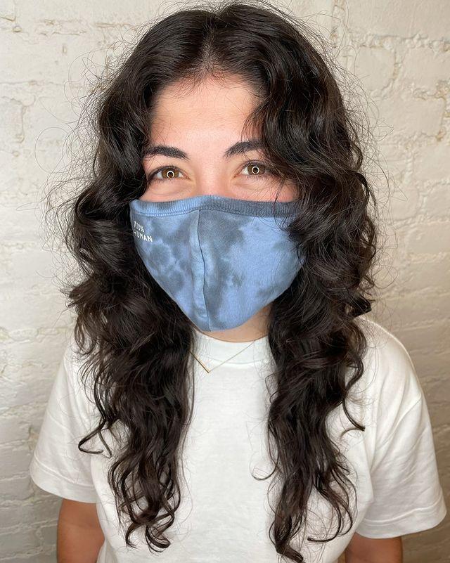 Jovem usando máscara de proteção azul e cobrindo sua expressão facial. Ela veste uma camiseta branca, pelo seu olhar parece sorridente.