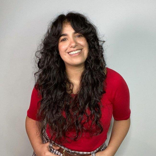Jovem sorridente posando com as mãos nos bolsos, em frente a uma parede branca, ela usa uma blusa vermelha.