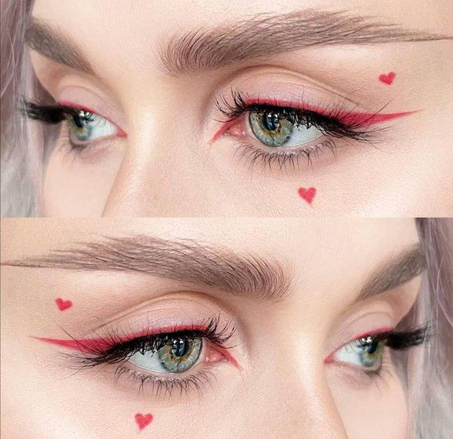 Imagem com foco no olhar de uma jovem que usa maquiagem com delineado rosa e coração pequeno no canto do olho.