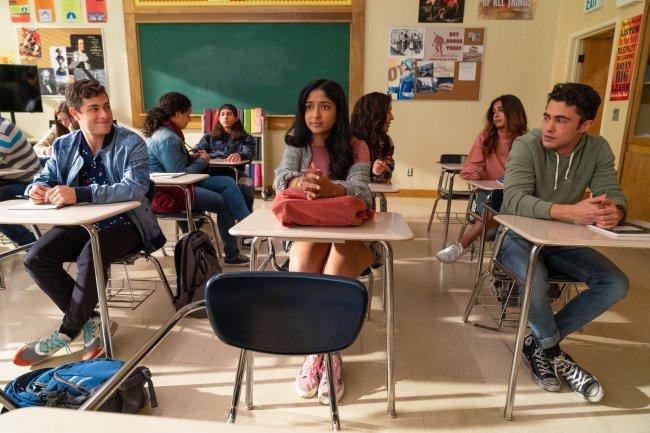 Devi na sala de aula; ela está sentada entre Ben e Paxton; os dois estão olhando para a protagonista mas ela olha para frente