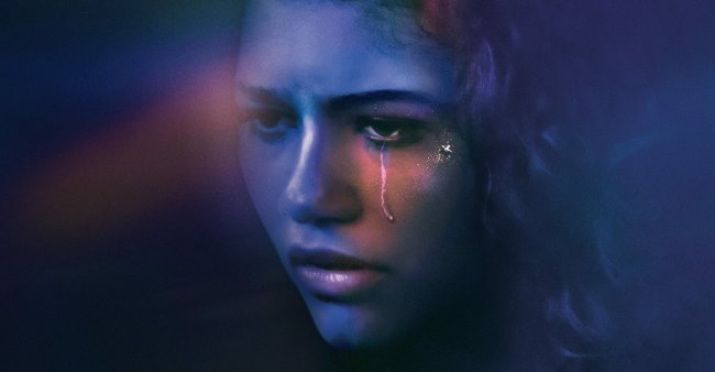 Foto do rosto da personagem Rue da série da HBO, Euphoria. Ela olha para frente, está com uma lágrima escorrendo no olho esquerdo e a fotografia tem tons de azul e roxo.