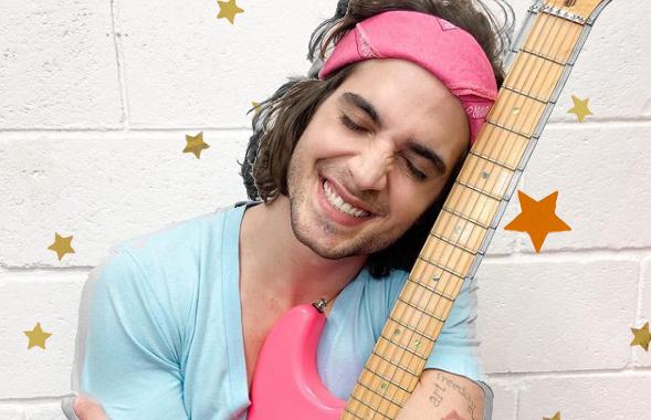 Fiuk abraçando sua guitarra rosa. Ele usa uma bandana rosa no cabelo também