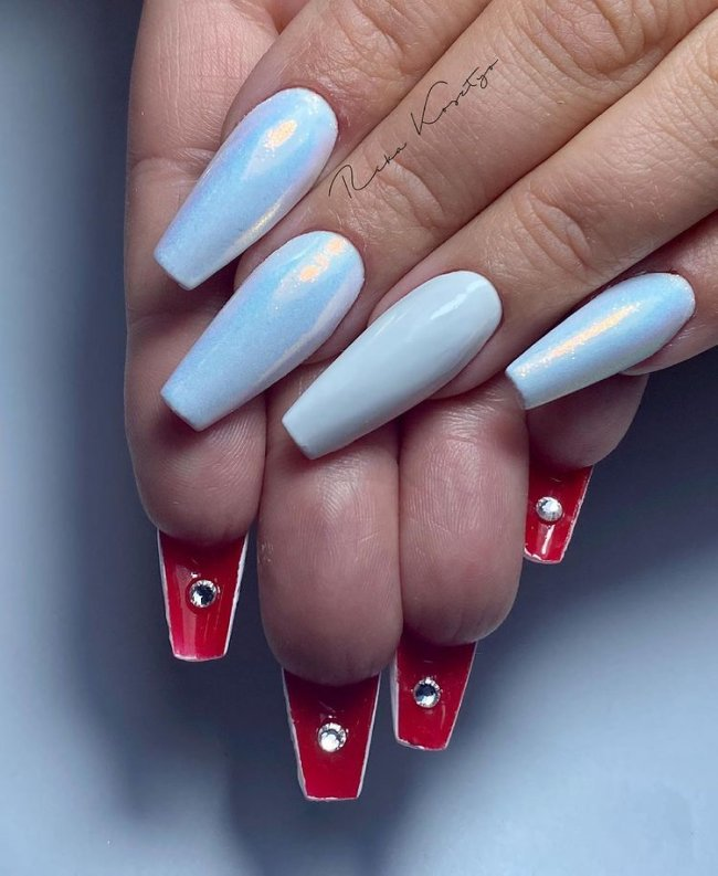 Foto com destaque para as mãos,unha flipside azul holográfica com interior vermelho com strass.