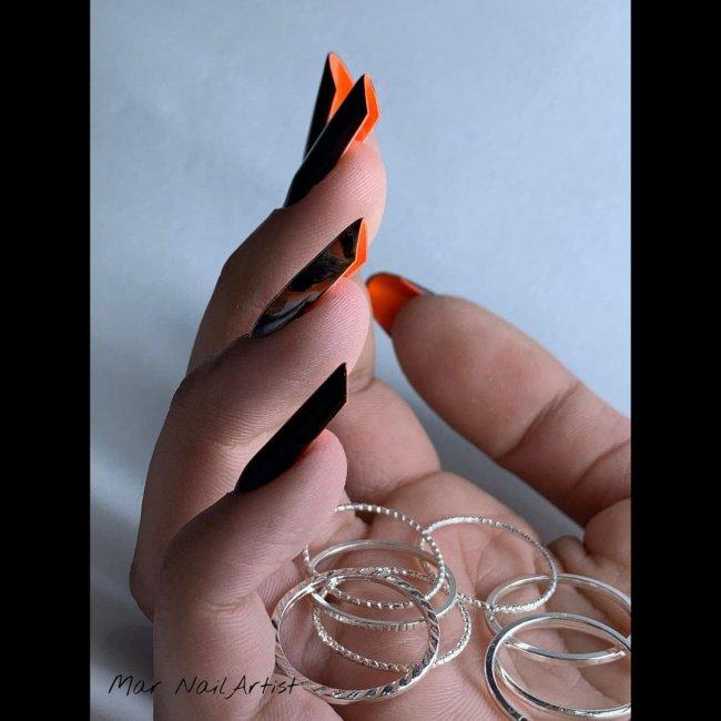 Foto com destaque para as mãos, unha flipside preta com interior laranja.
