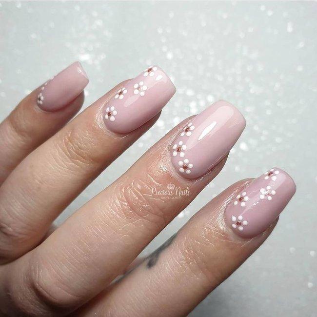 Foto com destaque nas unhas com nail art de bolinha, dessa vez com fundo bege e florzinha no canto inferior da unha.