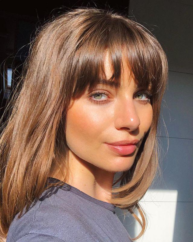 Selfie de uma mulher de perfil sorrindo levemente para a câmera. Ela usa uma blusa cinza, maquiagem natural e cabelo com franja desfiada solto.