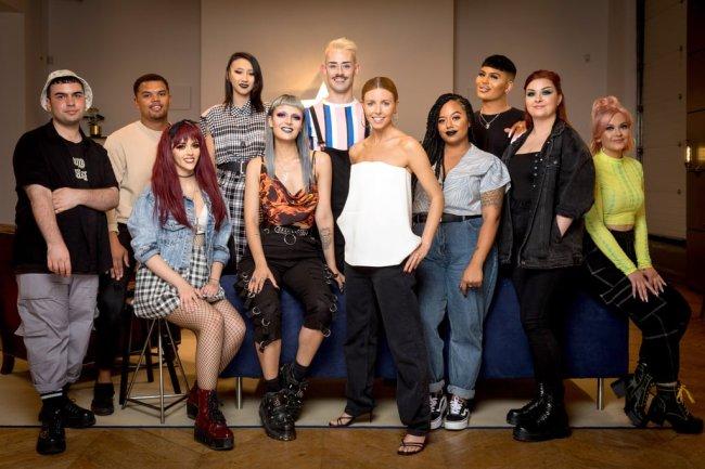 Foto do elenco do reality show de maquiagem da Netflix, Glow Up. Alguns participantes estão sentados e outros em pé, todos olham sorrindo para a câmera.