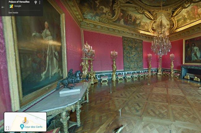 Imagem do Palácio de Versalhes, na França. O cômodo é rosa com detalhes dourados, e tem muitos lustres e quadros da realeza