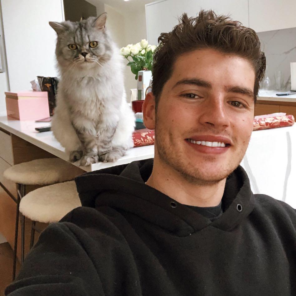 Gregg Sulkin posando para foto com gatinho branco e cinza; o ator está sorrindo e usando um moletom preto