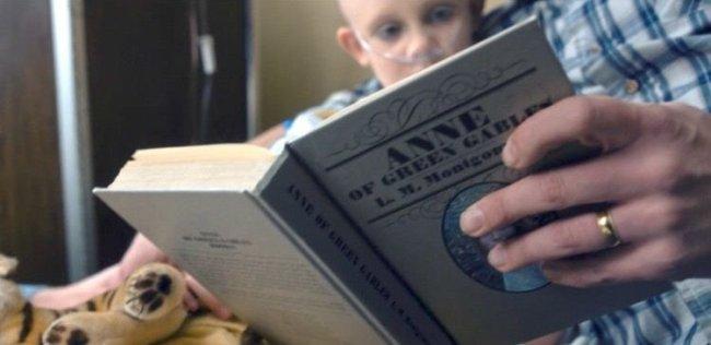 Ima mão, com uma alianaça, segura um livro. Ao fundo, uma menina, com aparelho respiratório, está sentada no colo da pessoa que lê e olha para o livro
