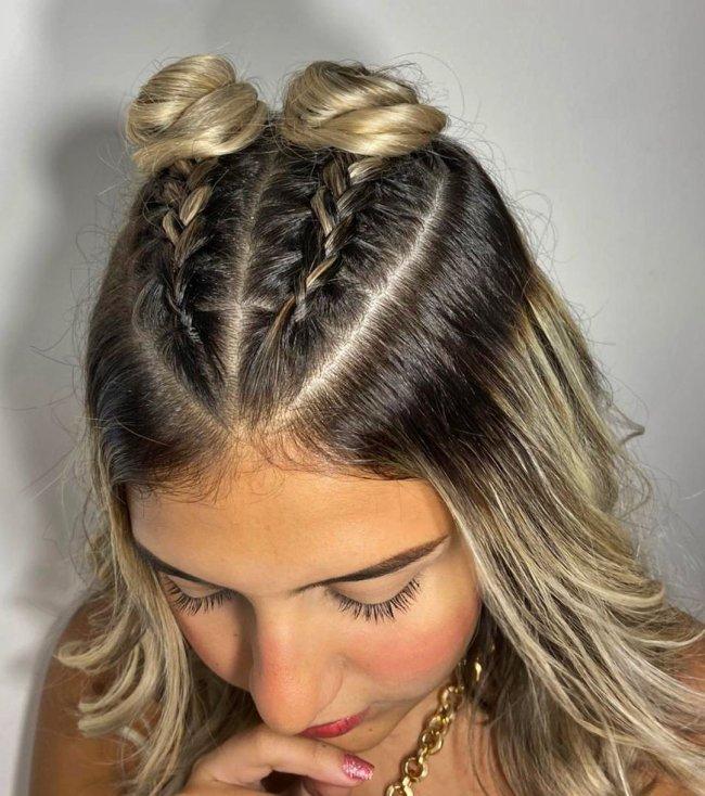 Jovem com a cabeça abaixada mostrando seu penteado, composto por dois coques e trancinhas.